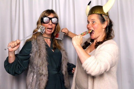 Two ladies posing for photo booth with many fun props