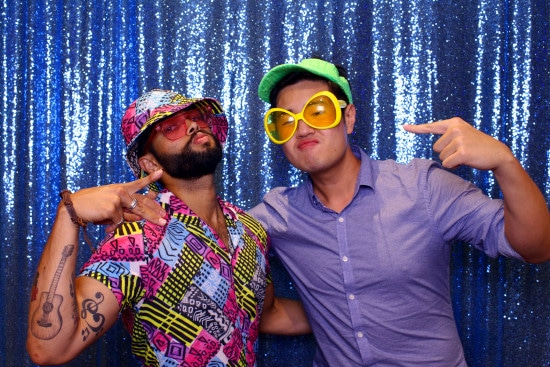 Two guys posing for photo booth with peace signs and colourful clothing