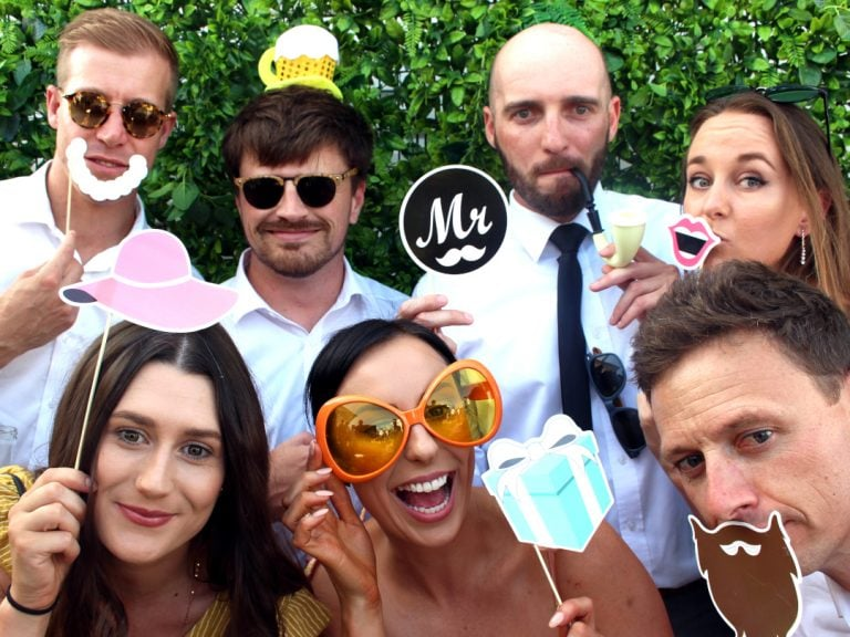 Seven wedding goers posing for photo booth shot.
