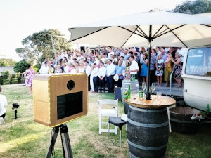 Photo booth set up in front of crowd at an outdoor wedding