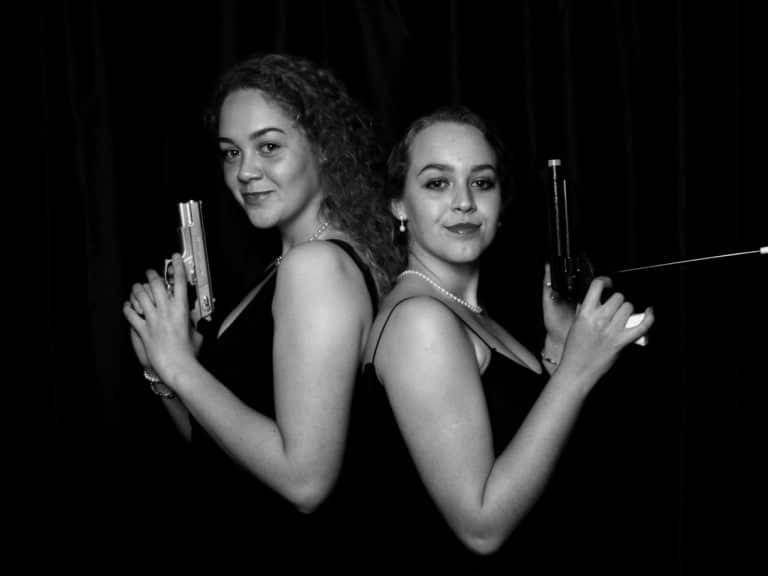Two girls back to back with gun props posing for photo booth shot