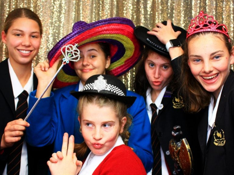 Five high school girls posing for photo booth shot with props.